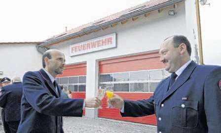 Wehrführer Rüdiger Linder und stellvertretender Wehrführer Jürgen Lang stoßen auf das neue Feuerwehrhaus an