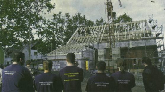 Feuerwehrleute beim Richtfest vor dem neuen Feuerwehrhaus
